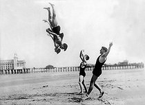 Acrobats making a somersault on a beach. © Albert Harlingue/Roger-Viollet