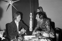 """Claude François (1939-1978), Egyptian-born French singer, and Hubert Wayaffe (born in 1938), French journalist and presenter, during the radio program """"Salut les Copains"""" on Europe N°1. Paris, 1963. © Noa / Roger-Viollet"""