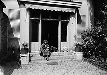 Colette (1873-1954), French writer and his dogs, in front of the house of boulevard Suchet, in Auteuil, who she lived from 1916 to 1928. About 1925. © Albert Harlingue/Roger-Viollet