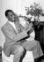 Nat King Cole (1919-1965), pianiste et chanteur de jazz américain, fumant à la pipe en verre de Bristol. Londres (Angleterre), Savoy Hotel, 21 mars 1954. © TopFoto / Roger-Viollet