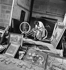 Paris, flea market. Market Biron. Woman repairing a bike among paintings for sale. © Pierre Jahan/Roger-Viollet