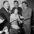 Edith Piaf (1915-1963), chanteuse française, avec son ami Doug Davies (1933-2014), peintre américain, et Bruno Coquatrix (1910-1979), directeur de salle de spectacle français. Aéoroport d'Orly, 1959. © Claude Poirier / Roger-Viollet