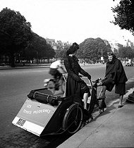 World War II. Fashion presentation in cycle-taxi, Paris.  © Laure Albin Guillot / Roger-Viollet