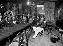 "The ""Lapin Agile"" cabaret. Meeting of Parisian artists among whom Poulbot, Dufy, Barrère, Neumont, Roubille, listening to old Frédé (playing the guitar). Paris, circa 1905.  © Albert Harlingue/Roger-Viollet"