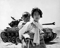 Korean War (1950-1953). With her brother on her back a war weary Korean girl tiredly trudges by a stalled M-26 tank, at Haengiu, Korea. June 9, 1951. (Navy) © US National Archives / Roger-Viollet