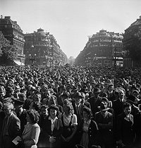 World War II. Liberation of Paris. Crowd listening to General de Gaulle's speech, broadcasted on the radio from the Chaillot palace. Paris (IXth arrondissement), Opéra Garnier, September 12, 1944. Photograph by Jean Roubier (1896-1981). © Fonds Jean Roubier/Roger-Vio
