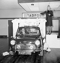 Peter Sellers (1925-1980) conduisant une mini Circassia bleu, cadeau d'anniversaire pour sa femme Britt Ekland (née en 1942), et sortant d'un gigantesque gâteau lors de la cérémonie d'ouverture de la nouvelle salle d'exposition de voiture Harold Radford. Londres (Angleterre), le 7 octobre 1965. © PA Archive/Roger-Viollet