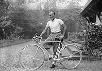 Tino Rossi (1907-1983), French actor and singer, posing next to his bicycle. © Roger-Viollet