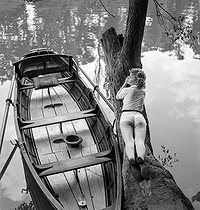 Young woman on a tree trunk and small boat on the river Marne. France, circa 1938-1939. © Gaston Paris / Roger-Viollet