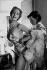 """Reportage sur les Folies-Bergère. Danseuse des Folies-Bergères se faisant aider par une habilleuse durant les répétitions de la revue menée par Yvonne Ménard, """"Une vraie folie"""". Paris, 1952. © Jacques Rouchon / Roger-Viollet"""
