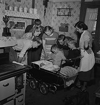 Family surrounding a newborn child. France, 1950. © Roger Berson/Roger-Viollet