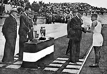 Military athletics competition in Vichy (France). Marshal Philippe Pétain presenting the cup to the winner of the 60 x 100 metres. On the left : François Darlan and Jean Borotra, August 1941. © LAPI/Roger-Viollet