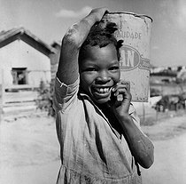 Undermined Geraes ( Brazil). Small girl carrying(wearing) some water. December, 1968. © Roger-Viollet