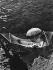 Jeune femme dans un hamac tendu au-dessus de la mer, avec une ombrelle. Cap Roux (Côte d'Azur), 1939. © Regina Relang/Ullstein Bild/Roger-Viollet