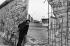 Chute du mur de Berlin. Homme regardant par un trou du mur près du Checkpoint Charlie. Allemagne, juin 1990. © Ullstein Bild / Roger-Viollet