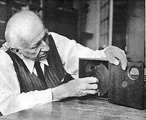 Louis Lumière (1864-1948), French industrialist, with the camera he invented in 1895 (for shooting and projection). 1943. © Roger-Viollet