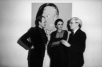 "Andy Warhol (1928-1987), American artist and director, with Mr and Mrs Sackler during the private viewing of the exhibition ""The American Indian Series"" at the Ace Gallery. Paris, 1976. © Jack Nisberg / Roger-Viollet"