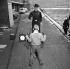 Brian Cole, âgé de 9 ans, tente de dégainer plus vite qu'un robot américain déguisé en policier fédéral. Londres (Angleterre), 7 février 1963. © TopFoto/Roger-Viollet