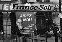 """Portrait of Abbé Pierre on a billboard of his charity campaign organised with the aid """"France-Soir"""", for Christmas, at the newspaper's head office. Paris, December 1984. © Carlos Gayoso/Roger-Viollet"""