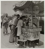 """World War II. US soldiers lining up in front of the ice-cream maker's stall """"Chez Emile"""" in front of the Eiffel Tower, view on the Trocadéro. Paris (VIIth and XVIth arrondissements), 1945. Photograph by Roger Schall (1904-1995). Paris, musée Carnavalet. © Roger Schall / Musée Carnavalet / Roger-Viollet"""