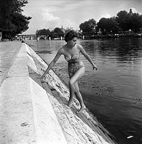 Young girl wearing a bikini on the banks of the Seine. Paris, July 1955. © Roger-Viollet