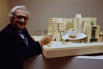 Frank Gehry (born in 1929), Canadian-born American architect, standing near a model of the American Center in Paris, inaugurated in 1993. Building now housing the Cinémathèque Française, the Film Library and the Film Archives. Paris, 1989. © Jean-Pierre Couderc / Roger-Viollet