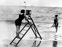 A woman photographer on the seashore. © Albert Harlingue/Roger-Viollet