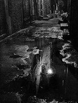 "Leiss Ferruccio. /caption/""Night puddles"" Street lights reflected in a puddle, Venice//caption//datePhoto/1950 ca.//datePhoto//artist///artist/. 00000000. © Leiss Ferruccio / Alinari / Roger-Viollet"