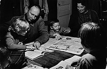 Parents keeping an eye on their children's homework. Burgundy (France), 1963. Photograph by Janine Niepce (1921-2007). © Janine Niepce / Roger-Viollet