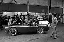 "Actors of the ""New Wave"" surrounding the AC Bristol car on the set of ""Les Tricheurs"", film by Marcel Carné. From left to right: Alain Delon, Jean-Claude Brialy, Andréa Parisy, Laurent Terzieff, Bernadette Lafont, Jeanne Valérie, Gérard Blain, Juliette Mayniel. France, April 1959. © Bernard Lipnitzki / Roger-Viollet"