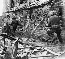 World War II. Battle of Normandy. British infantrymen walking along a house during the fights, July-August 1944. © LAPI/Roger-Viollet