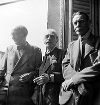 "World War II. Liberation of Paris. Victory celebration. Paul Valéry (1871-1945) and Georges Duhamel (1884-1966), French writers, and André Siegfried (1875-1959), French sociologist, geographer and historian, attending the General de Gaulle's parade on the Champs-Elysées from the building of ""Le Figaro"" newspaper. Paris (VIIIth arrondissement), on August 26, 1944. Photograph by Jean Roubier (1896-1981). © Fonds Jean Roubier/Roger-Vio"