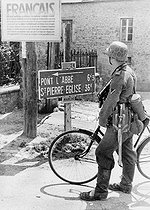 World War II. Normandy front. German soldier in front of a sign encouraging the French to repel the Allies, June 1944. © LAPI/Roger-Viollet