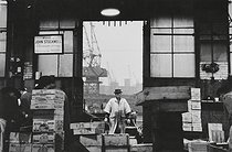 Fish hall at the Billingsgate Market. The man is wearing a leather hat passed down from generation to generation. London (England), 1958. © Jean Mounicq/Roger-Viollet