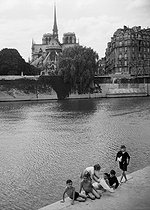 Children bathing in the river Seine in front of the Notre-Dame de Paris Cathedral. Paris, 1956. Photograph by Janine Niepce (1921-2007). © Janine Niepce / Roger-Viollet