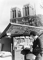 Young woman at the stall of a secondhand bookseller near the Notre-Dame cathedral. Paris, circa 1935. © Collection Roger-Viollet / Roger-Viollet