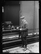 """World War I. Daylight saving time in France, during the night of June 14-15, 1916. Train conductor looking at his watch. Photograph published in the newspaper """"Excelsior"""", on June 14, 1916. © Wackernie / Excelsior - L'Equipe / Roger-Viollet"""