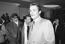 """Alain Delon (born in 1935), French actor, and Maurice Béjart (1927-2007), French dancer and choreographer, attending the premiere of """"Kean"""". Paris, Théâtre Marigny, February 1987. © Carlos Gayoso / Roger-Viollet"""