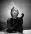 """Bibi Ejad, garni de fleurs artificielles et d'un ample noeud de tulle, photographié pour le magazine """"Fémina"""". Paris, janvier 1938. © Boris Lipnitzki/Roger-Viollet"""