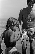 Alain Delon (born in 1935), French actor, on the beach with his son Anthony (born in 1964), 1968. Photograph by Georges Kelaïditès (1932-2015). © Georges Kelaïditès / Roger-Viollet