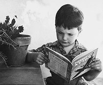 4-year old boy reading a comic book. France, 1950. Photograph by Janine Niepce (1921-2007). © Janine Niepce/Roger-Viollet