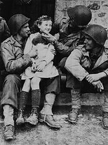 World War II. Normandy front. US soldiers with a French girl in a liberated city, on June 27, 1944. © Collection Roger-Viollet / Roger-Viollet
