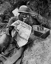 Korean War (1950-1953). Clarence Whitmore, radio operator of the 24th regiment ofthe US Army, reading the Stars and Stripes newspaper during his lunch. Surroundings of Sangju (South Korea), on August 9, 1950. © US National Archives / Roger-Viollet