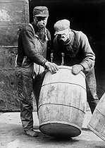World War One. Workers handling a barrel of chlorinated lime, wearing masks protecting then from choking gas. France, 1917. © Jacques Boyer/Roger-Viollet