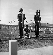 Korean War (1950-1953). A little Korean girl places a wreath of flowers on the grave of an American soldier, while Pfc. Chester Painter and Cpl. Harry May presents arms, at the United Nations cemetery in Pusan. April 9, 1951. (Army) © US National Archives / Roger-Viollet