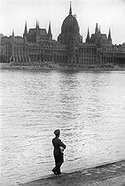 Soldier carrying a child and Hungarian Parliament Building, on the banks of the Danube river. Budapest (Hungary), 1954. Photograph by Jean Marquis (1926-2019). © Jean Marquis / Roger-Viollet