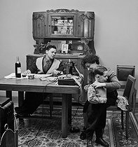 Workers' family life. Amother trying on a pattern on her son while her husband is reading a newspaper. Paris, 1952. © Jacques Rouchon/Roger-Viollet