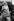 """Le prince Charles, la princesse Anne et Elisabeth Bowes-Lyon saluant le vice-amiral A.G.V. Hubback, avant de monter à bord du """"Britannia"""". Portsmouth (Angleterre), 14 avril 1954. © TopFoto/Roger-Viollet"""