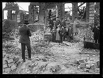 "Passengers of a ""tourist train"" who carried 750 people across the battefields and devastated cities, posing among the ruins, on May 11, 1919. Photograph published in the newspaper ""Excelsior"" on Monday, May 12, 1919. © Excelsior – L'Equipe/Roger-Viollet"