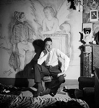 Jean Cocteau (1889-1963), French writer, under a decor designed by Christian Bérard (1887-1971), French painter and decorator (1932), 1934.      © Boris Lipnitzki / Roger-Viollet